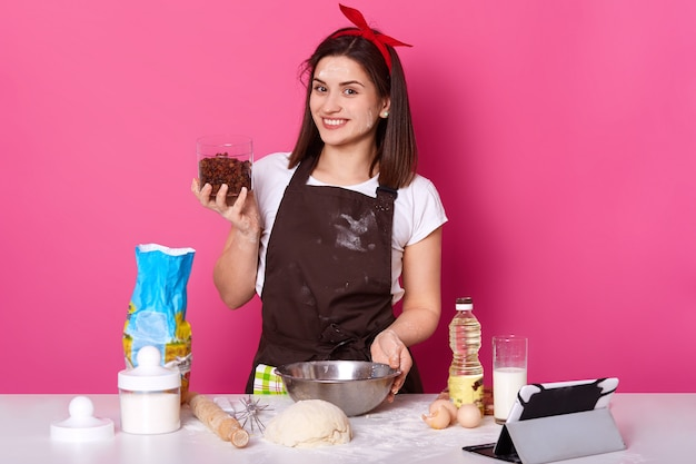 Jeune cuisinière brune se tient à la cuisine tenant le récipient avec des raisins secs, souriant sincèrement, mélangeant les ingrédients dans un bol. charmante mignonne dame positive développe ses compétences culinaires en essayant une nouvelle recette.
