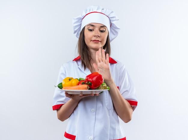 Jeune cuisinière mécontente portant un uniforme de chef tenant des légumes sur une assiette montrant un geste d'arrêt isolé sur fond blanc