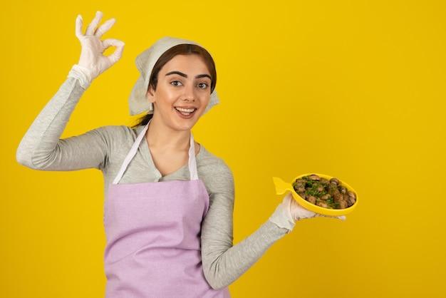 Jeune cuisinière en tablier tenant une assiette de champignons frits et montrant un signe ok.