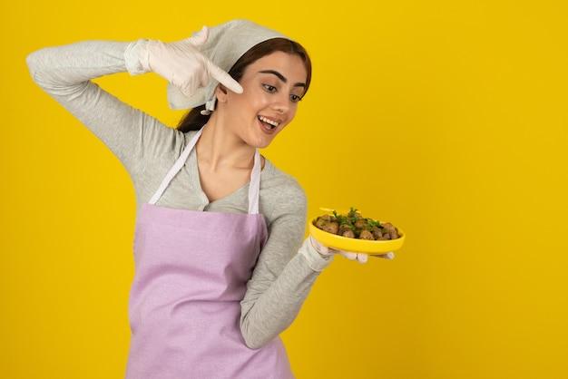 Jeune cuisinière en tablier tenant une assiette de champignons frits sur un mur jaune.