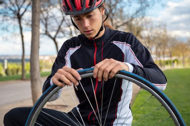 Jeune cycliste cool en vêtements de sport et casque de protection réparant la chambre à air de la roue de vélo dans le parc