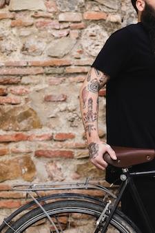 Jeune cycliste, debout, contre, mur brique