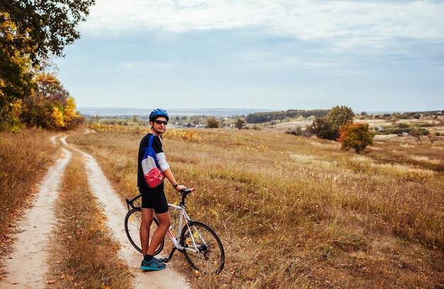 Jeune cycliste se reposant dans un champ d'automne