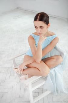 Jeune danseur de ballet moderne posant sur mur blanc
