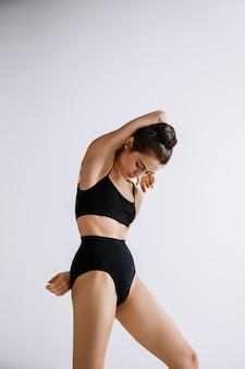 Jeune danseuse de ballet en body noir contre le mur blanc du studio