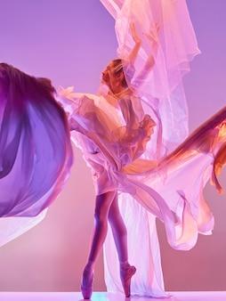 Jeune danseuse de ballet gracieuse ou ballerine classique dansant au studio rose