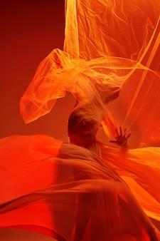 Jeune danseuse de ballet gracieuse ou ballerine classique dansant au studio rouge. modèle caucasien sur pointes