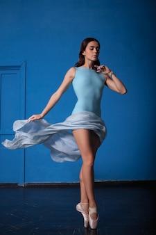 Jeune danseuse de ballet moderne posant sur bleu