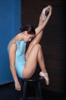 Jeune danseuse de ballet moderne posant sur fond bleu