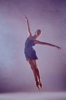 Jeune danseuse de ballet sautant sur un fond lilas. ballerine porte une robe bleue et des pointes. le tir de contour - silhouette de fille avec effet de fumée