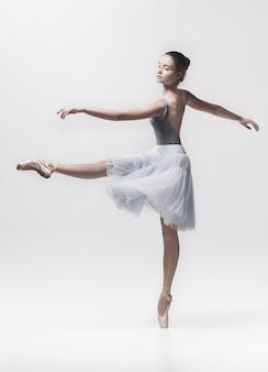 Jeune danseuse classique danse sur blanc