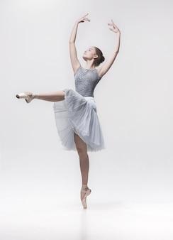 Jeune danseuse classique isolée sur blanc.