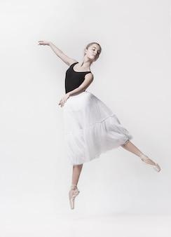 Jeune danseuse classique isolée sur espace blanc.
