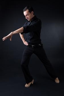Jeune danseuse de flamenco dans une belle robe sur fond noir.