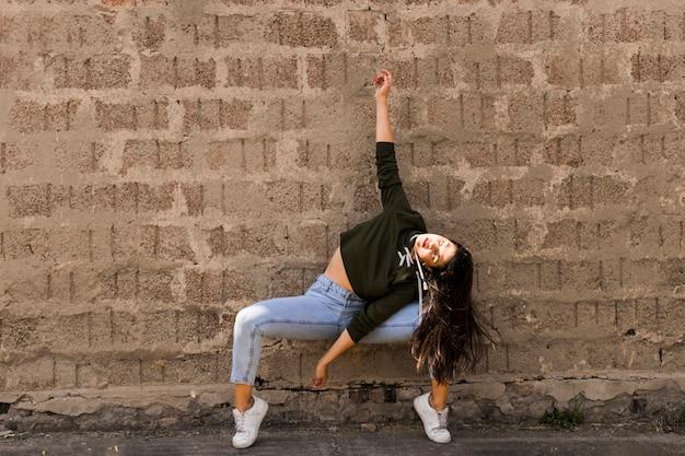 Jeune danseuse moderne dansant devant le mur de grunge