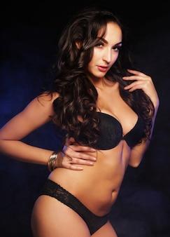 Jeune danseuse de strip-tease sur le noir, l'amour et la passion