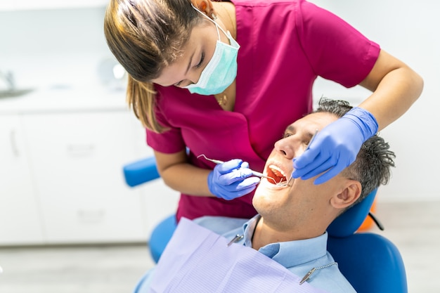 Jeune dentiste femme faisant un contrôle jusqu'à un patient.