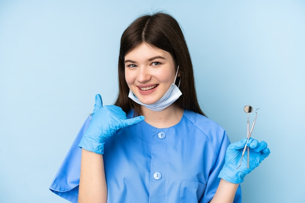 Jeune, dentiste, femme, tenue, outils, isolé, bleu, mur, confection, téléphone, geste