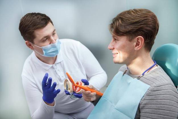 Jeune dentiste masculin portant un masque médical, parlant à son patient