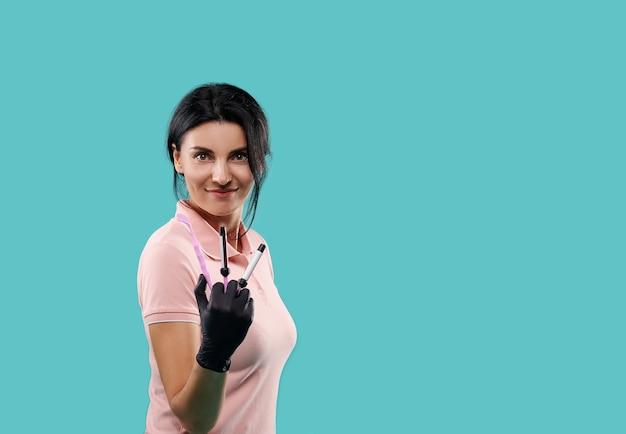 Jeune dentiste portant l'uniforme rose et des gants en latex médical noir tenant des outils dentaires isolés sur fond bleu avec copie espace