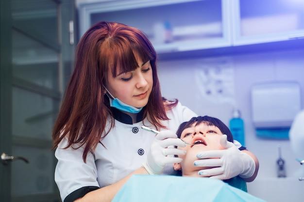 Jeune dentiste rousse à la clinique avec un patient