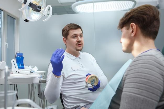 Jeune dentiste travaillant dans sa clinique, parler à un patient