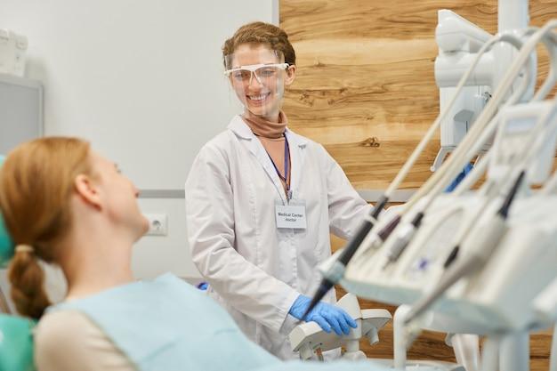 Jeune dentiste travaillant avec du matériel médical et parlant au patient qui se trouve sur une chaise dentaire