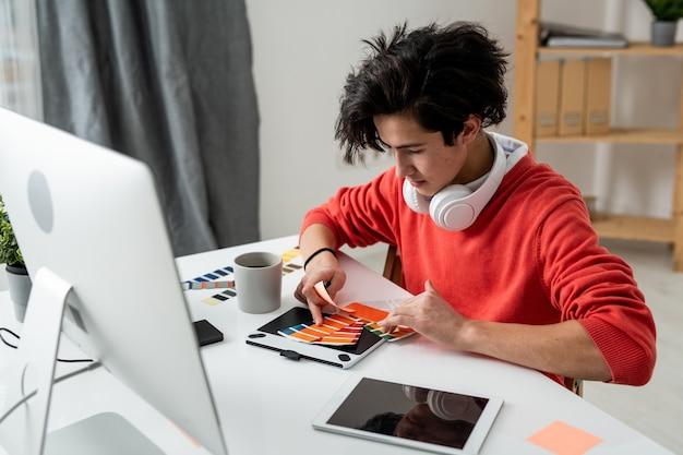 Jeune designer contemporain en tenue décontractée assis par lieu de travail à la maison et en choisissant la couleur de la palette