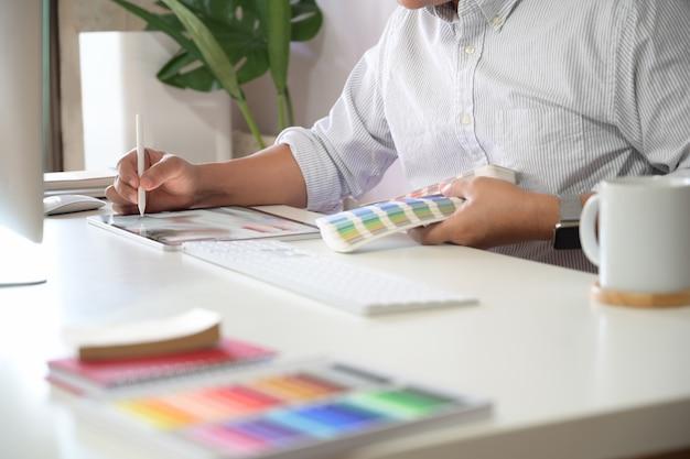 Jeune designer dessinant des croquis sur une tablette graphique au bureau de studio.