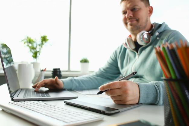 Un jeune designer détient un stylo de tablette à la main travaillant sur un nouveau projet pour le client dans le domaine des projets de construction de bâtiments