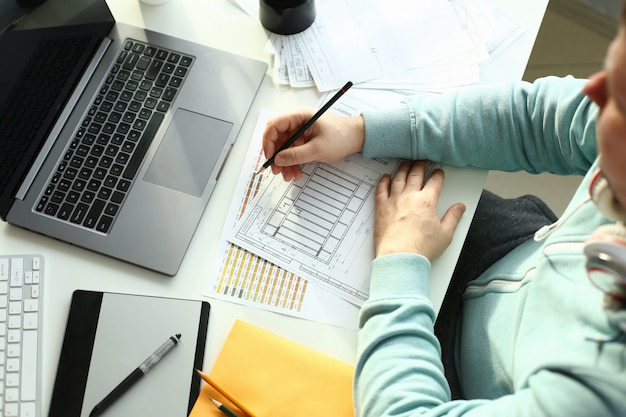 Un jeune designer est titulaire d'un stylo à partir d'une tablette dans son