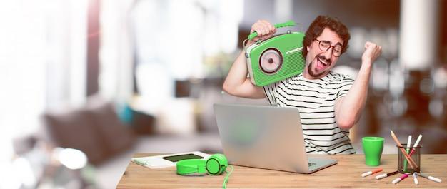 Jeune designer graphique fou sur un bureau avec un ordinateur portable