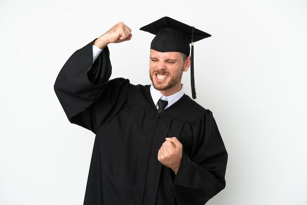 Jeune diplômé brésilien d'université isolé sur fond blanc célébrant une victoire