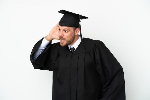 Jeune diplômé brésilien d'université isolé sur fond blanc écoutant quelque chose en mettant la main sur l'oreille
