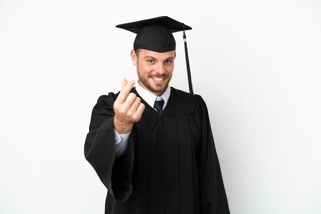 Jeune diplômé brésilien d'université isolé sur fond blanc faisant un geste d'argent