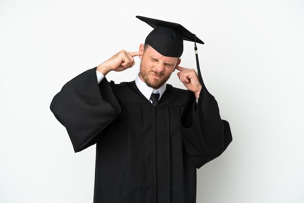 Jeune diplômé brésilien d'université isolé sur fond blanc frustré et couvrant les oreilles