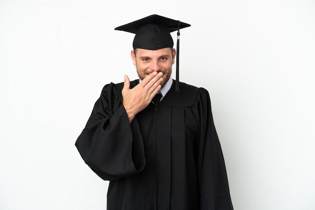Jeune diplômé brésilien d'université isolé sur fond blanc heureux et souriant couvrant la bouche avec la main