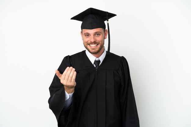 Jeune diplômé brésilien d'université isolé sur fond blanc invitant à venir avec la main. heureux que tu sois venu