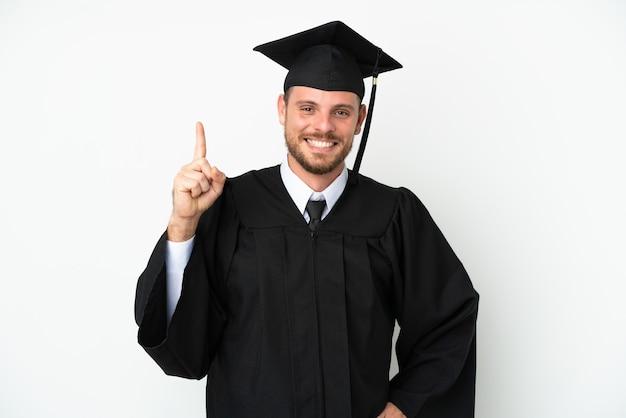 Jeune diplômé brésilien d'université isolé sur fond blanc montrant et levant un doigt en signe du meilleur