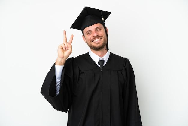 Jeune diplômé brésilien d'université isolé sur fond blanc souriant et montrant le signe de la victoire