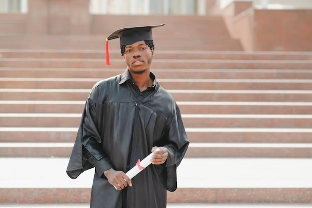 Jeune diplômé de sexe masculin africain debout devant le bâtiment de l'université