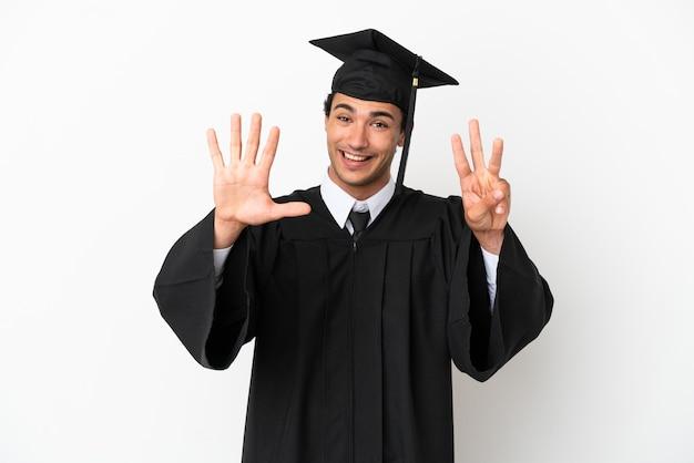 Jeune diplômé universitaire sur fond blanc isolé comptant huit avec les doigts