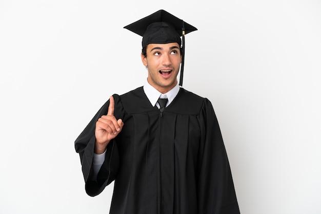 Jeune diplômé universitaire sur fond blanc isolé pointant vers le haut et surpris