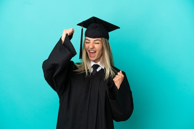 Jeune diplômé universitaire sur fond bleu isolé célébrant une victoire