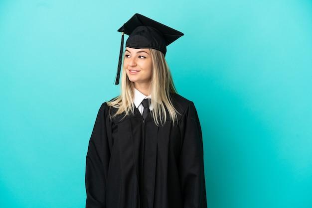 Jeune diplômé universitaire sur fond bleu isolé regardant sur le côté et souriant