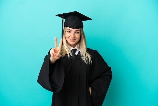 Jeune diplômé universitaire sur fond bleu isolé souriant et montrant le signe de la victoire