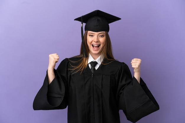 Jeune diplômé universitaire sur fond violet isolé célébrant une victoire en position de vainqueur