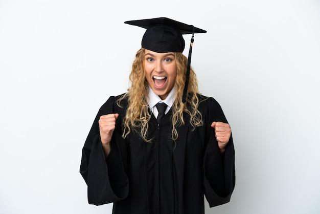 Jeune diplômé universitaire isolé sur fond blanc célébrant une victoire en position de vainqueur