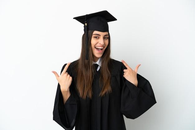 Jeune diplômé universitaire isolé sur fond blanc donnant un coup de pouce geste