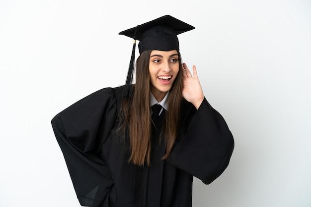Jeune diplômé universitaire isolé sur fond blanc écoutant quelque chose en mettant la main sur l'oreille